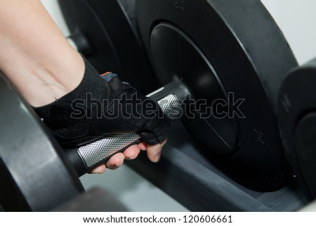female hand is holding metal barbell
