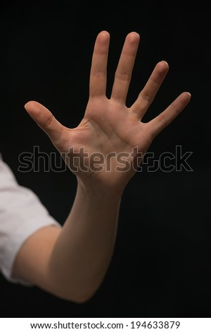 Female hand is showing five fingers isolated on black background - stock photo