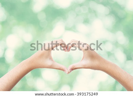 Female Hand love Signal with beautiful green nature background. - stock photo