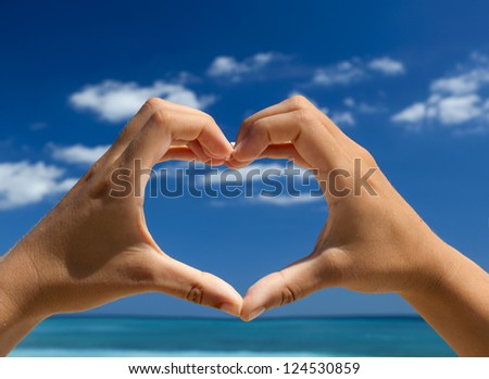 Female hand making a heart shape against a beautiful blue sky - stock photo