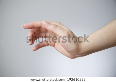 Female hand on a gray background. Copy space - stock photo