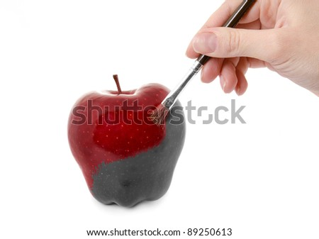 Female hand painting a fresh red apple which is partly black and white and partly colored, isolated on white background