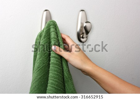 Female hand picking up a towel - stock photo