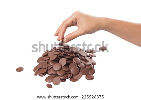 Female hand picking up chocolate button over white background - stock photo