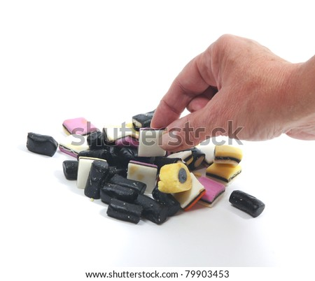 Female hand picks a liquorice from stack - stock photo