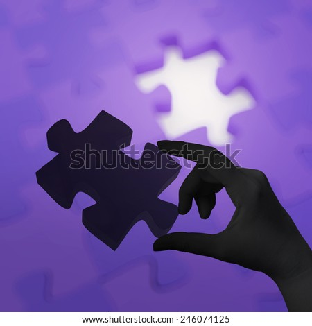 female hand placing last piece of Puzzle as concept - stock photo