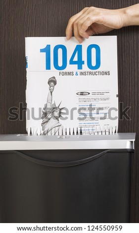 Female hand placing personal income tax form cover page into paper shredder - stock photo