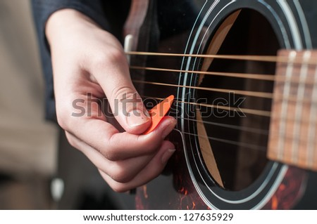 Female hand playing acoustic guitar.guitar play.Close up of guitarist hand playing acoustic guitar - stock photo