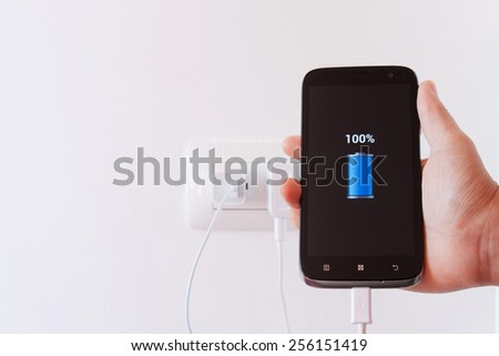 female hand plugging in the wall electtric plug of her smartphone in a socket - stock photo