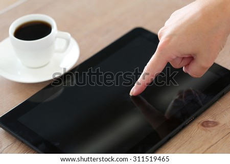 Female hand pointing in black tablet pc and using it closeup with cup of coffee in background. Mobile computer with touch screen lying on table. Popular gadget, modern lifestyle business life concept - stock photo
