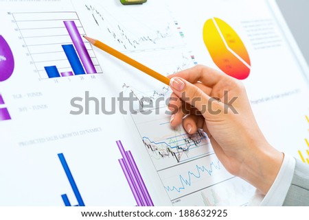female hand pointing pencil on financial charts, paper work in the office