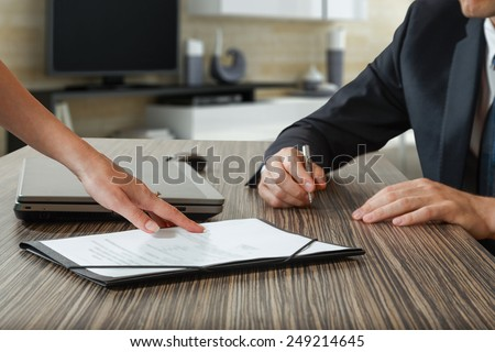 female hand pointing to businessman at signature place on a contract document - stock photo
