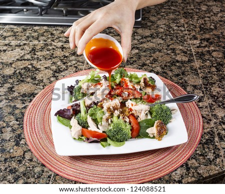 Female hand pouring salad dressing onto vegetable salad with smoked salmon with place mat and stone kitchen counter top underneath white dinner plate - stock photo