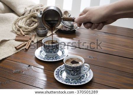 Female Hand Pouring Turkish Coffee   - stock photo