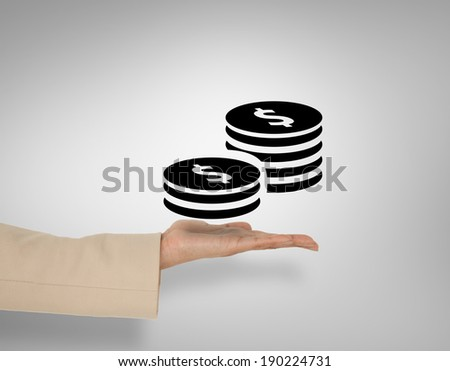 Female hand presenting dollar coins against grey vignette - stock photo