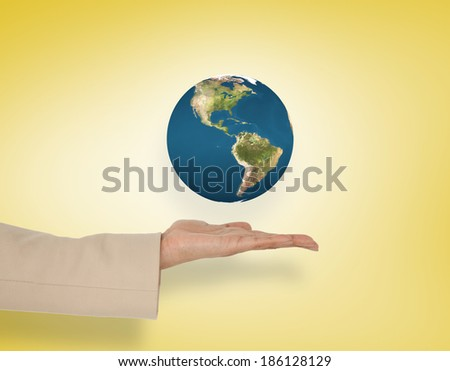 Female hand presenting earth against yellow vignette, elements of this image furnished by NASA
