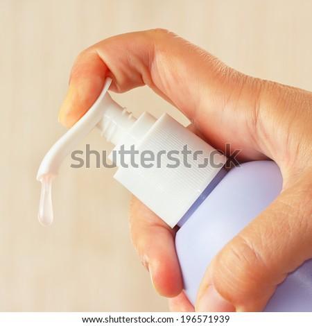 Female hand presses the antibacterial liquid soap dispenser - stock photo