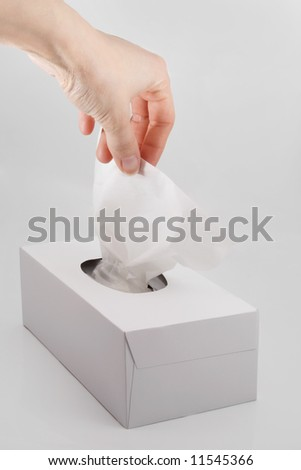 female hand pulling white facial tissue from a box - stock photo
