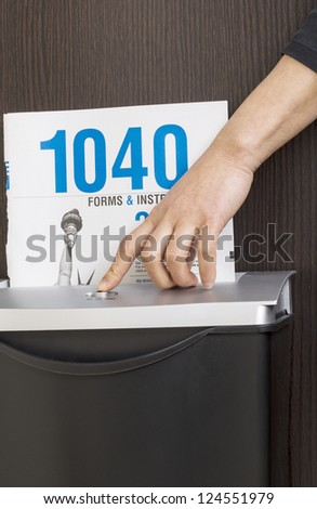 Female hand pushing on button of shredder to shred personal income tax form - stock photo