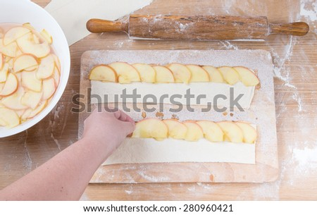Female hand puts apple slices on the dough strip on a light wooden table with flour. - stock photo