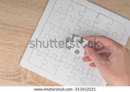 Female hand putting a missing piece and solving blank white jigsaw puzzle placed on top of old wooden oak table, top view, close up, selective focus