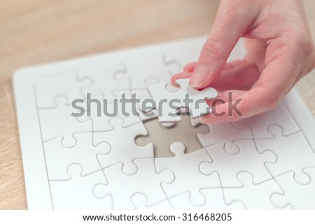 Female hand putting a missing piece and solving blank white jigsaw puzzle placed on top of old wooden oak table, close up, selective focus