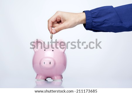 Female hand putting coin into a piggy bank over gray background - stock photo