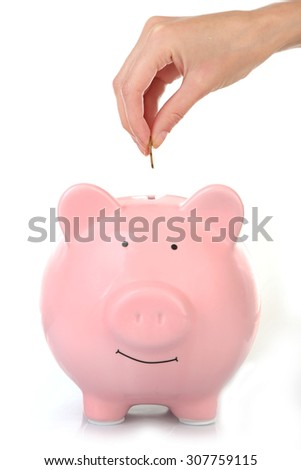 Female hand putting coin into piggy bank isolated on white - stock photo