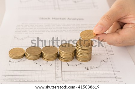 Female hand putting coin on coins stack with the report analyzes economic trends in background. Finance, Investment Concepts.