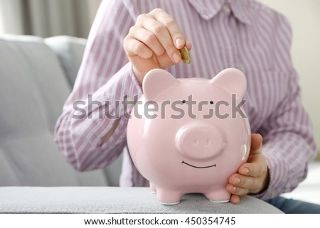 Female hand putting money into piggy bank indoors
