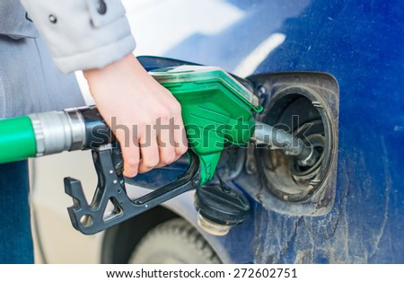 Female hand refueling dirty blue car. - stock photo