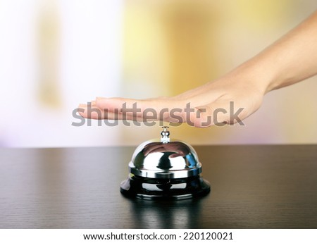 Female hand ring bell on  hotel reception desk, on bright background - stock photo