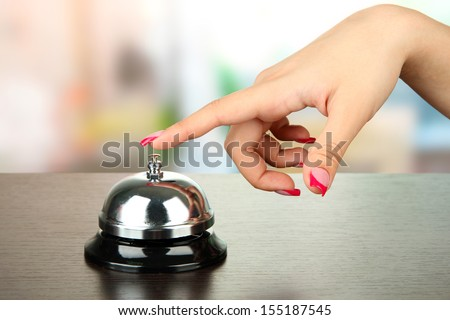 Female hand ringing in service bell on bright background - stock photo