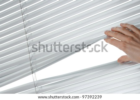 Female hand separating slats of venetian blinds to see through.