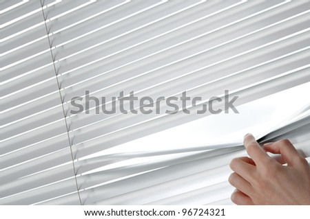 Female hand separating slats of venetian blinds with a finger to see through. - stock photo