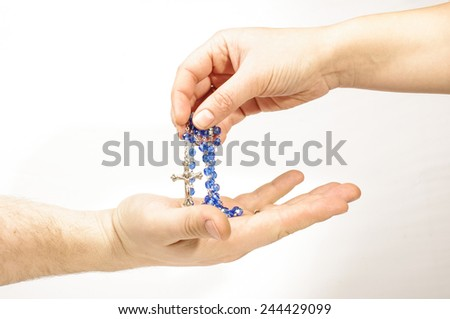 Female hand sharing rosary religion togetherness concept - stock photo