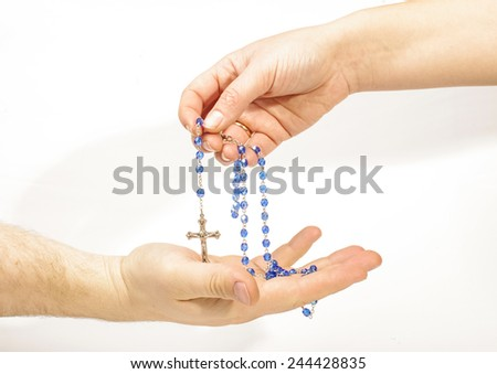 Female hand sharing rosary with male hand - stock photo