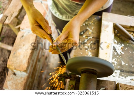Female hand sharpening tool with a Circular Sharpener - stock photo