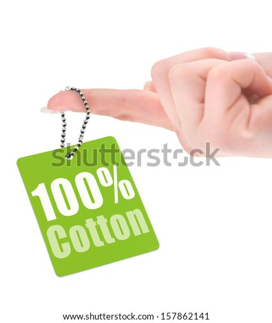 female hand showing hundred percent cotton tag isolated on white background - stock photo