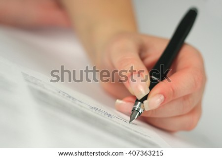Female hand signing a contract, shallow DOF