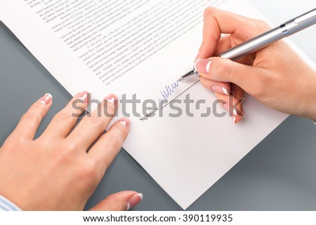 Female hand signing business papers. Close-up of woman signing document. Here's the final word. Point of no return. - stock photo