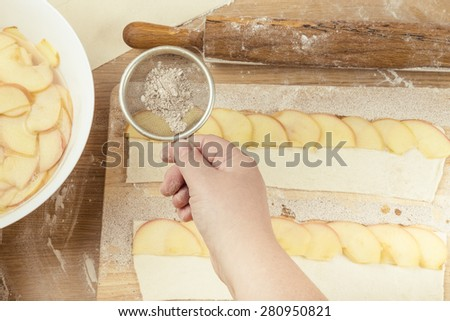 Female hand sprinkles apple slices on the dough strip on a light wooden table with flour. Toned. - stock photo