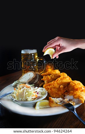 Female Hand squeezing lemon on tasty looking fish fry dish, with tall glass of beer in the background - stock photo