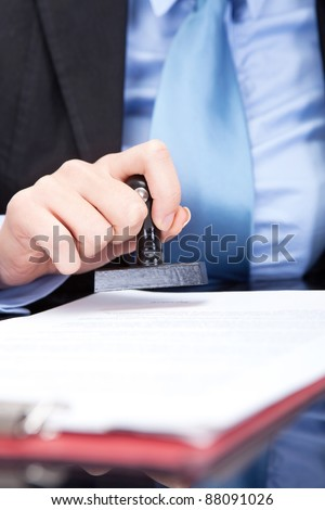 female hand stamping document, close up - stock photo