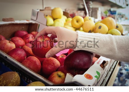 Female hand taking fruit from a shelf - stock photo