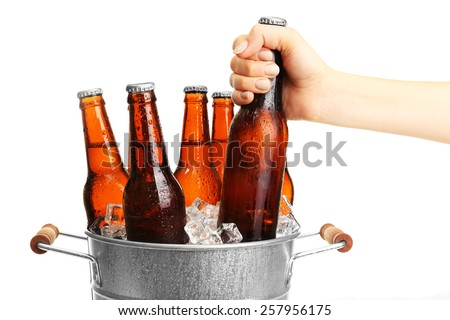 Female hand taking glass bottle of beer from metal bucket isolated on white