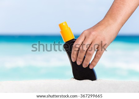 Female hand taking sunscreen protection cream from white sand against turquoise caribbean sea water. Tropical summer vacation concept - stock photo