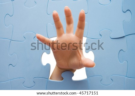 Female hand through a puzzle - stock photo
