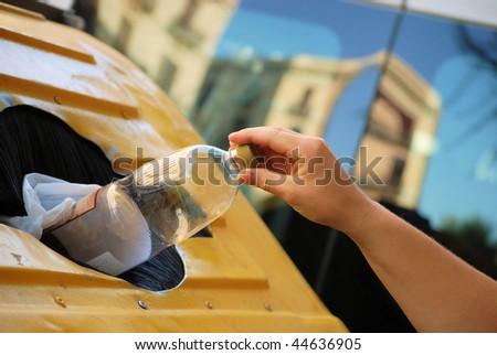 female hand throwing out a plastic large bottle in container for processing and recycling - stock photo