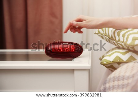 Female hand trying to stop digital clock ringing - stock photo